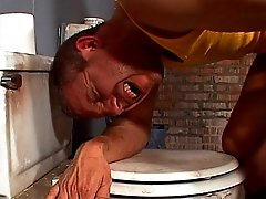 Bent over a dirty toilet, this horny fuck has his ass reamed and then drinks hot sperm
